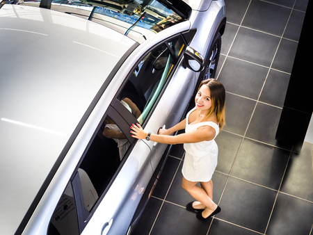Nice girl standing near the new car in the showroom. Buying new cars concept Reklamní fotografie