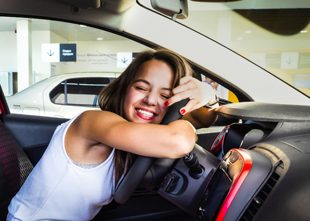 Nice girl sitting in the new car in the showroom. Buying new cars concept