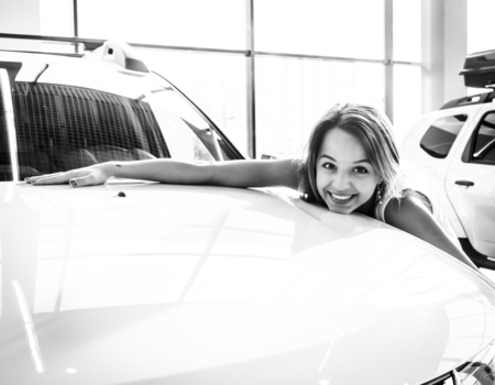 Young female driver embracing hood of new car. Dream about car. Gorgeous smiling woman hugging lies on the hood of new red car in the dealership. Black and white shot