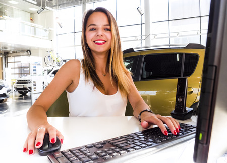 Young woman working at the modern office desk with a laptop, busy with distance learning, tutoring, making online surveys. Lady boss at her workplace. Business success concept. People at work concept