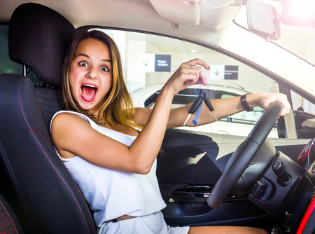 Young pretty woman happy and smiling, holding the keys of the white car, confident, offering them to start your new car