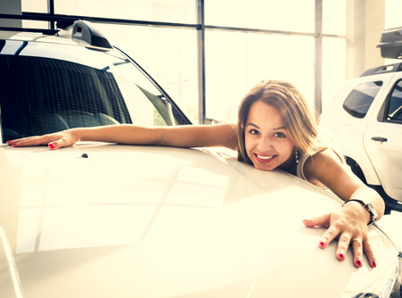 Young female driver embracing hood of new car. Dream about car. Gorgeous smiling woman hugging lies on the hood of new red car in the dealership.