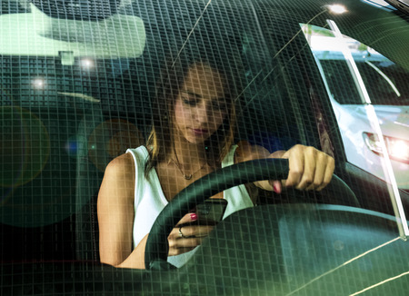 Young woman holding mobile phone while driving car. Female driver hand on steering wheel and checking out her smartphone in moving vehicle. Do not text and drive concept. Close up, background.