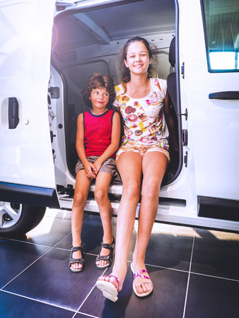 Cute teen girl sitting in a minibus with a sliding door. The joy of buying a new family car concept. Reklamní fotografie