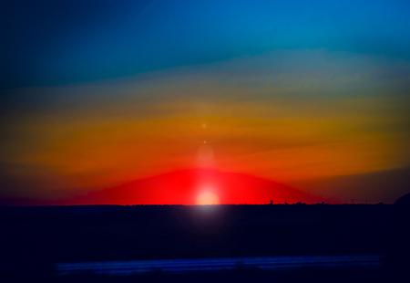 Half of the sun during sunrise on warm sky background Banco de Imagens