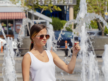 A girl shoots a city fountain holding a waterproof camera under water jets.