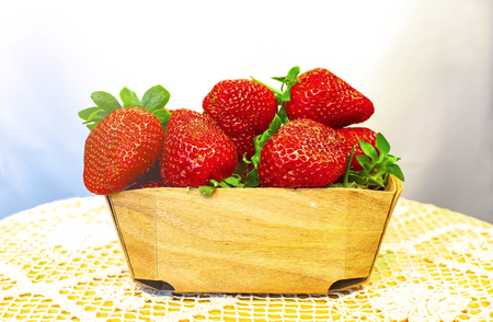 Basket of ripe fresh strawberries standing on a table covered with a lace tablecloth, healthy concept
