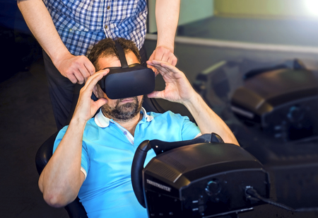 Mature bearded man wears VR glasses. Gamer plays VR race on a dark room gaming club. Virtual reality on car simulator. A man is sitting behind a car simulator and plays games. Reklamní fotografie - 122504024