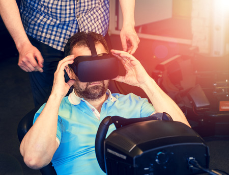 Mature bearded man wears VR glasses. Gamer plays VR race on a dark room gaming club. Virtual reality on car simulator. A man is sitting behind a car simulator and plays games.