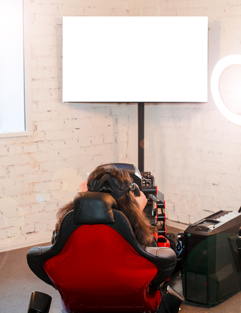 The girl sits in the simulator of a car with a VR headset on the head and plays the game. The woman plays the race in a virtual reality room gaming club. Back view. Copy space Banco de Imagens