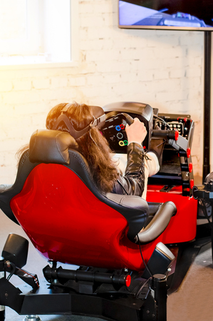 The girl sits in the simulator of a car with a VR headset on the head and plays the game. The woman plays the race in a virtual reality room gaming club. Back view