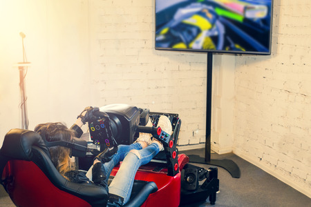 The girl sits in the simulator of a car with a VR headset on the head and plays the game. The woman plays the race in a virtual reality room gaming club. Back view. Selective focus.