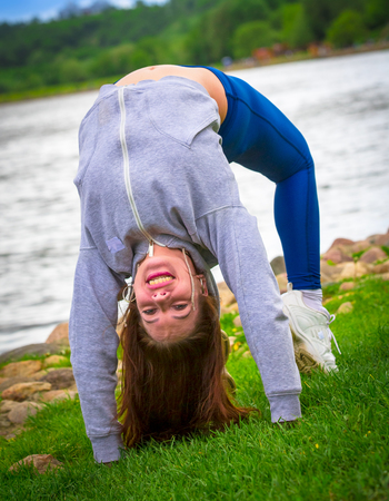 young girl goes in for sports in nature. healthy lifestyle.flaxible child doing joga poses bridge streching in the nature Reklamní fotografie - 124627362