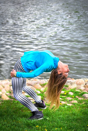 young girl goes in for sports in nature. healthy lifestyle.flaxible child doing joga poses bridge streching in the nature. Warm-up on the shore of a natural pond, river, lake, sea.Copy space