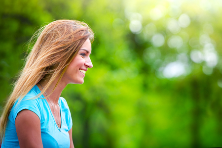 Portrait of beautiful girl in profile close-up in the wind. Portrait of girl in profile against green summer nature.Copy space