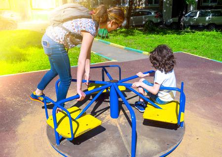 Image of joyful friends having fun on carousel outdoors Reklamní fotografie