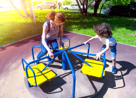 Image of joyful friends having fun on carousel outdoors Banco de Imagens