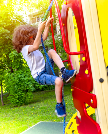 Little curly boy is playing on playground. Happy shaggy kid boy having fun and climbing on outdoor playground. Funny joyful child using the rope. Summer, spring and autumn leisure for active kids.