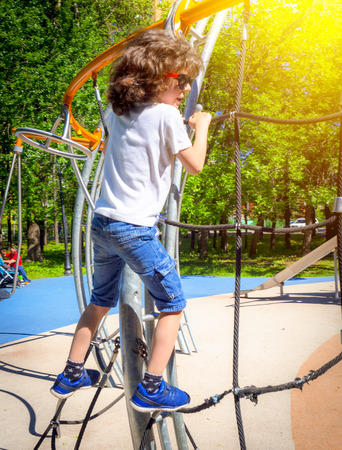 Boy playing playground equipment. Active little child playing on climbing net at school yard playground. Kids play and climb outdoors on a sunny summer day Reklamní fotografie - 124627551