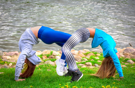 Two Caucasian Females in tights and sneakers Doing Yoga Exercises on the background of the river. Practicing and creating a showy composition while standing in the pose of an athletes bridge.