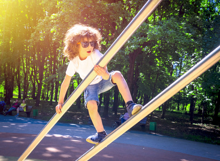 Boy is climbing on iron pipes on the playground Reklamní fotografie - 124675123