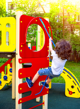 Little curly boy is playing on playground. Happy shaggy kid boy having fun and climbing on outdoor playground. Funny joyful child using the rope. Summer, spring and autumn leisure for active kids. Reklamní fotografie - 124754899
