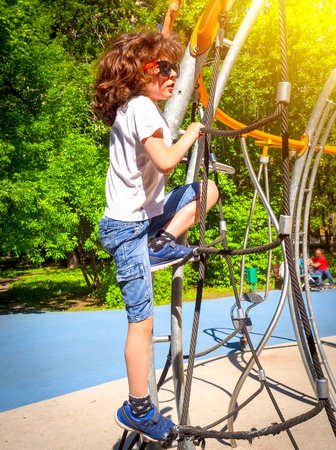 Boy playing playground equipment. Active little child playing on climbing net at school yard playground. Kids play and climb outdoors on a sunny summer day