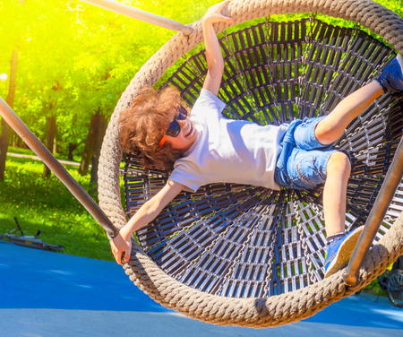 Cheerful boy swinging in the swing-nest. Entertainment for preschoolers outdoors Reklamní fotografie - 124754906
