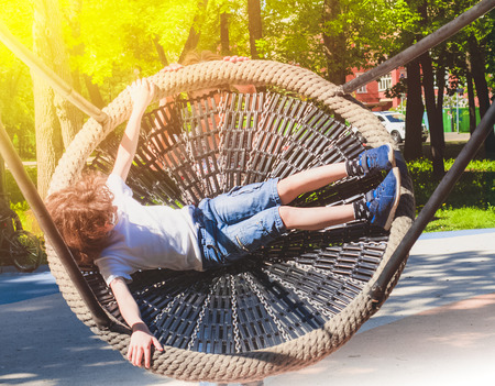 Cheerful boy swinging in the swing-nest. Entertainment for preschoolers outdoors