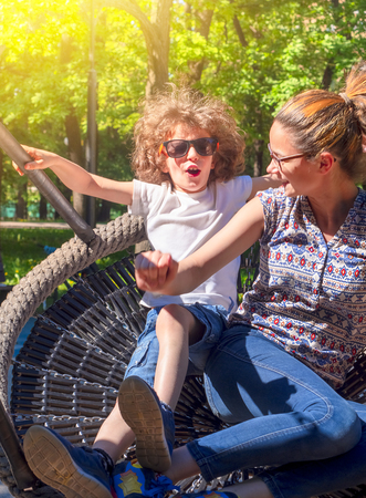 Little laughing family of two children swing on swing. Happy childchood concept image.