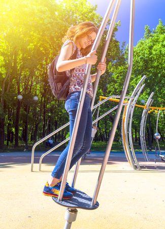 Adult girl on the playground have fun during summer vacation in the summer park