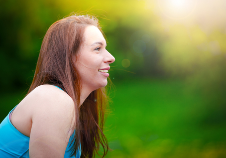 Portrait of girl in profile against green summer nature.Portrait of a smiling young woman in woodland. Copy space