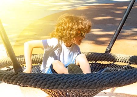Cheerful boy swinging in the swing-nest. Entertainment for preschoolers outdoors Reklamní fotografie - 124627682