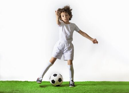 Boy with soccer ball on the green grass.Excited little toddler boy playing football on soccer field against light background. Active childhood and sports passion concept. Save space Standard-Bild - 129258909