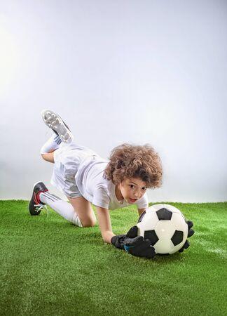 Auf dem Rasen liegender Torhüter fängt einen Ball. Aufgeregter kleiner Kleinkindjunge, der Fußball auf Fußballplatz vor hellem Hintergrund spielt. Aktives Konzept für Kindheit und Sportleidenschaft. Platz sparen