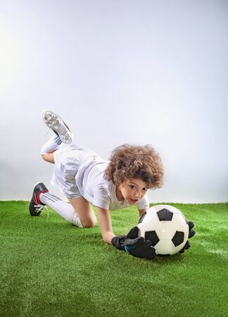 Goalkeeper lying on the grass catches a ball. Excited little toddler boy playing football on soccer field against light background. Active childhood and sports passion concept. Save space Stockfoto