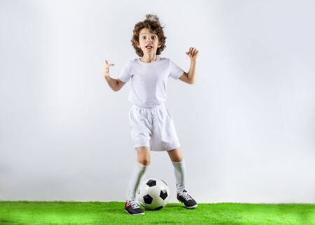Boy with soccer ball on the green grass.Excited little toddler boy playing football on soccer field against light background. Active childhood and sports passion concept. Save space Standard-Bild - 129258983