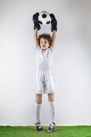 Boy with soccer ball on the green grass.Excited little toddler boy playing football on soccer field against light background. Active childhood and sports passion concept. Save space Standard-Bild - 129258995
