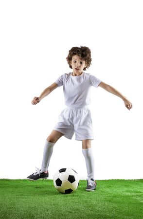Boy with soccer ball on the green grass.Excited little toddler boy playing football on soccer field against light background. Active childhood and sports passion concept. Save space Standard-Bild - 129259003