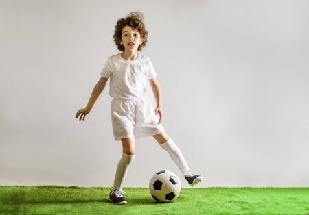 Boy with soccer ball on the green grass.Excited little toddler boy playing football on soccer field against light background. Active childhood and sports passion concept. Save space Standard-Bild - 129258970