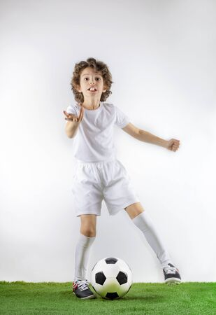 Boy with soccer ball on the green grass.Excited little toddler boy playing football on soccer field against light background. Active childhood and sports passion concept. Save space Standard-Bild - 129259005