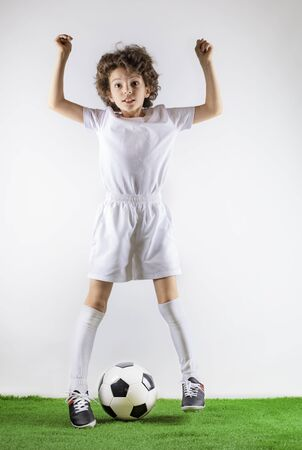Boy with soccer ball on the green grass.Excited little toddler boy playing football on soccer field against light background. Active childhood and sports passion concept. Save space Standard-Bild - 129258998