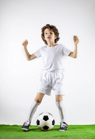 Boy with soccer ball on the green grass.Excited little toddler boy playing football on soccer field against light background. Active childhood and sports passion concept. Save space Standard-Bild - 129259011
