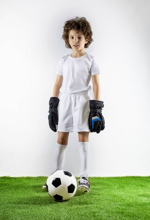 Boy with soccer ball on the green grass.Excited little toddler boy playing football on soccer field against light background. Active childhood and sports passion concept. Save space