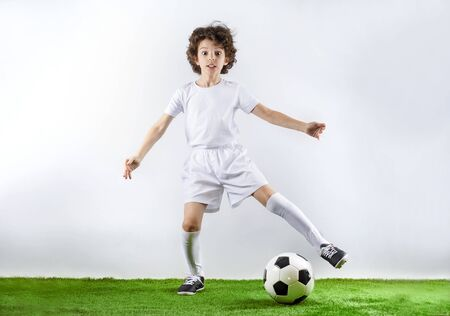 Boy with soccer ball on the green grass.Excited little toddler boy playing football on soccer field against light background. Active childhood and sports passion concept. Save space Standard-Bild - 129259010
