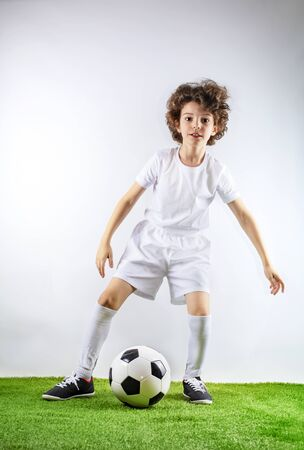 Boy with soccer ball on the green grass.Excited little toddler boy playing football on soccer field against light background. Active childhood and sports passion concept. Save space Standard-Bild - 129259062