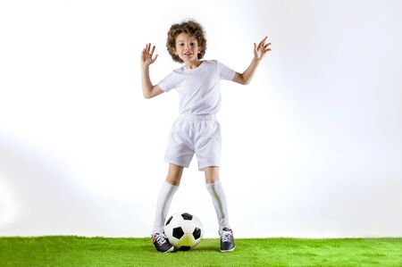 Boy with soccer ball on the green grass.Excited little toddler boy playing football on soccer field against light background. Active childhood and sports passion concept. Save space Standard-Bild - 129259063