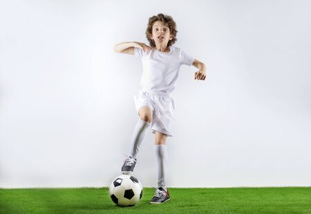 Boy with soccer ball on the green grass.Excited little toddler boy playing football on soccer field against light background. Active childhood and sports passion concept. Save space Standard-Bild - 129259064