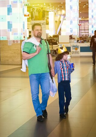 MOSCOW, RUSSIA - MAY 30, 2019: Dad and son going shopping walking around the supermarket. They have a great time together. Редакционное