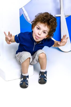 Little captain. Boy plays seaman. Child and sea wheel. Child and yacht mock. Boy posing in studio. Standard-Bild - 129259074